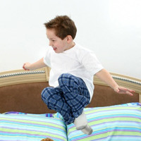 Five year old boy in pajamas jumping in bed.