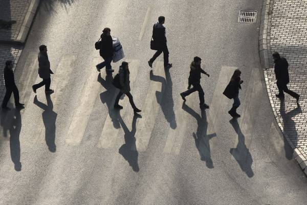 Pedestrians cast their shadows as they cross a street in Pristina.