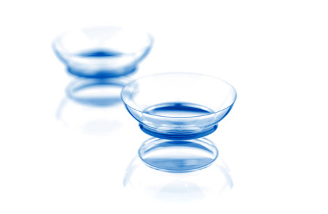 Two contact lenses with reflections, isolated on a white background