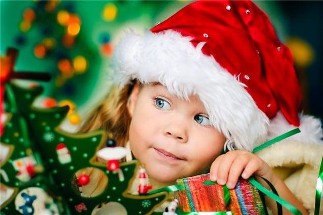 Bambina che cerca i regali di Natale